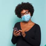Covid-19 Cuidado e Prevenção. Descrição da imagem: Moça com máscara de proteção usando um celular.